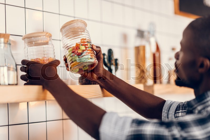 Stock image of 'cropped view of african american barista holding glass jars and working on bar counter in cafe '