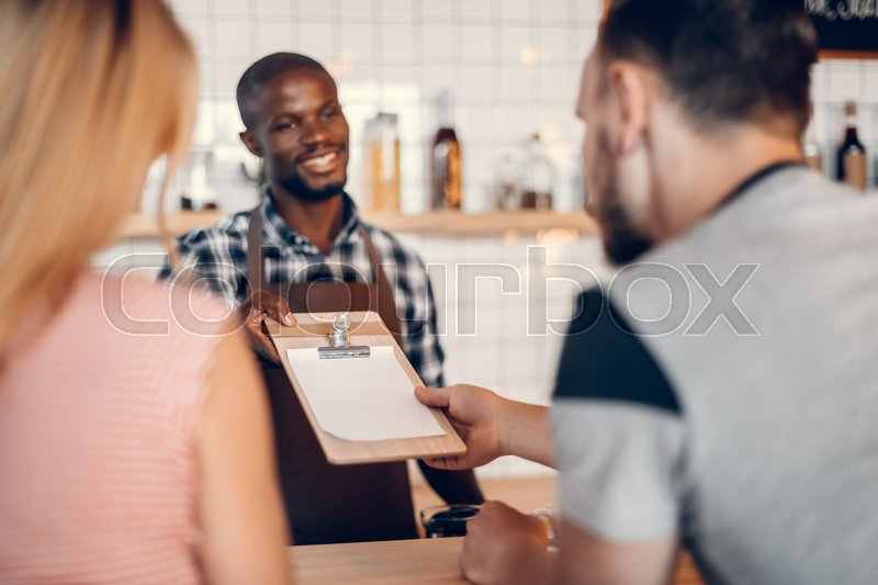 Stock image of 'handsome cheerful african american barista giving menu to clients on bar counter in cafe '