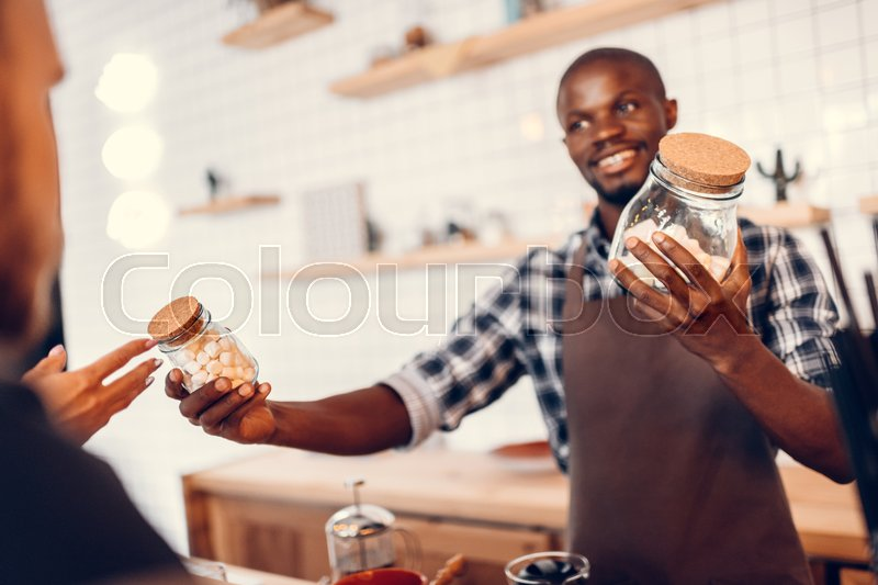 Stock image of 'handsome cheerful african american barista holding glass jars with marshmallows on bar counter in cafe '
