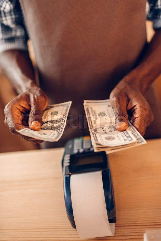 Stock image of 'cropped view of african american barista with terminal counting money in cafe '