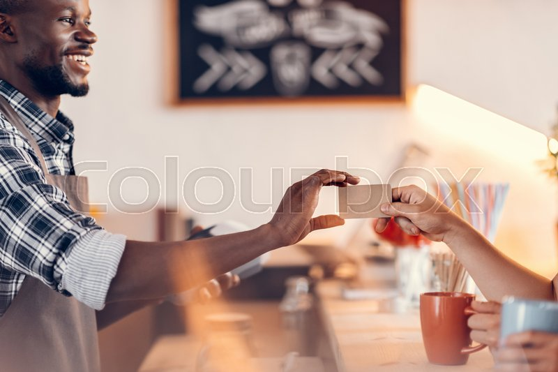 Stock image of 'handsome smiling african american barista taking credit card for payment on bar counter in cafe '