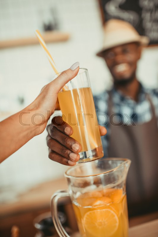 Stock image of 'stylish african american bartender giving glass of lemonade to woman in cafe '