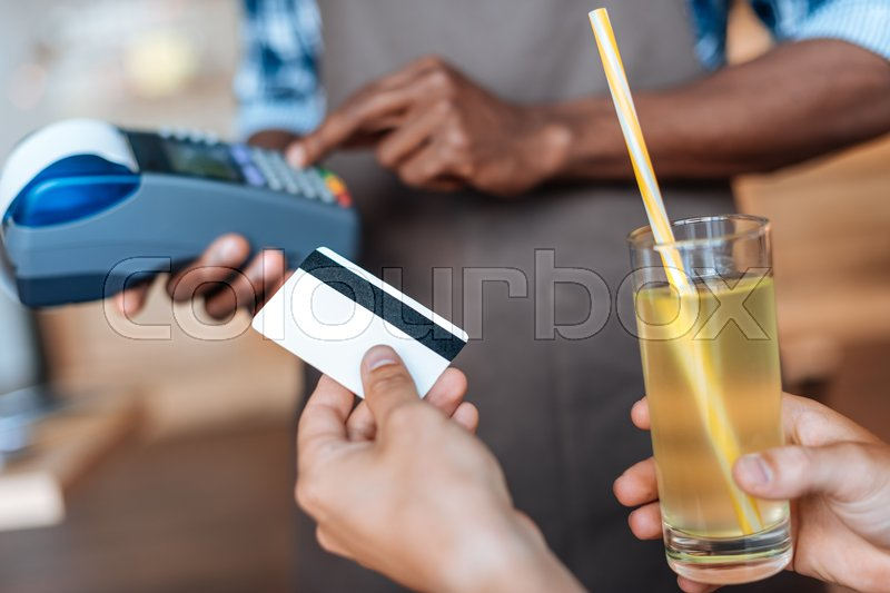 Stock image of 'cropped view of person paying with credit card, waiter with terminal standing behind in cafe  '