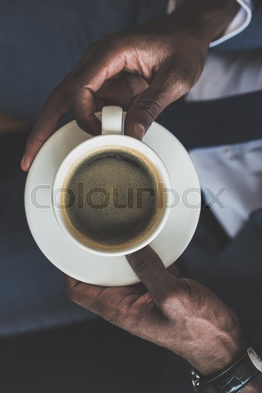 Stock image of 'top view of african american man holding cup of coffee in cafe '
