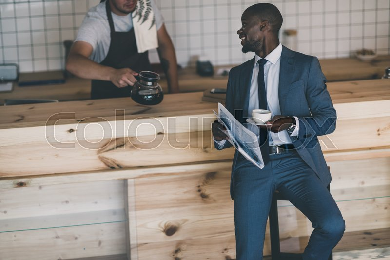 Stock image of 'african american businessman standing with newspaper on coffee break in cafe '