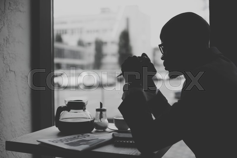 Stock image of 'Silhouette of african american businessman working during coffee break in cafe, black and white'