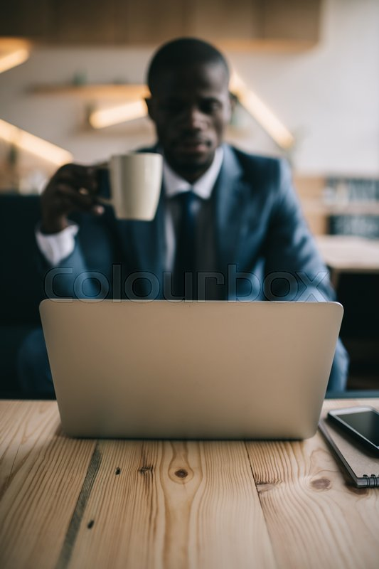 Stock image of 'selective focus of african american businessman working with laptop during coffee break in cafe '