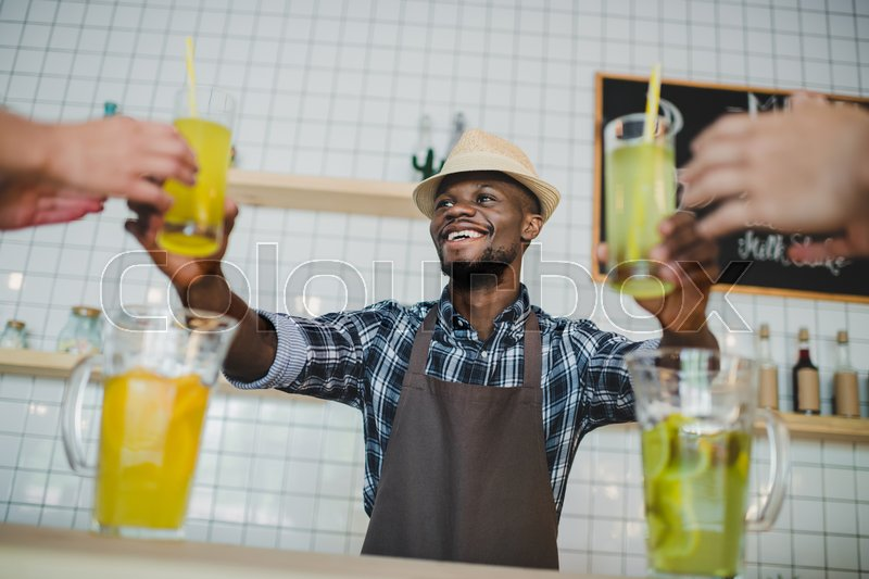 Stock image of 'stylish smiling african american bartende giving glasses of lemonade in cafe '