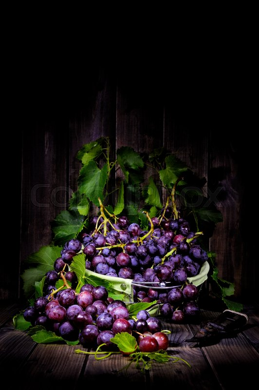 Stock image of 'Fresh red grapes bunch lying on leaves on an old wooden table. Photographed with light painting technique'