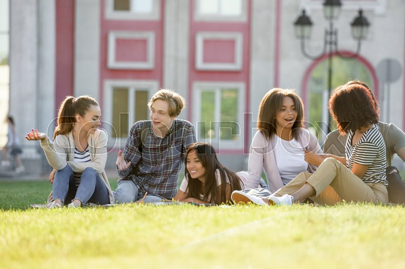 Stock image of 'Image of multiethnic group of young concentrated students studying outdoors. Looking aside.'