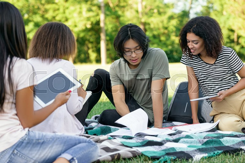 Stock image of 'Picture of multiethnic group of young concentrated students studying outdoors. Looking aside.'