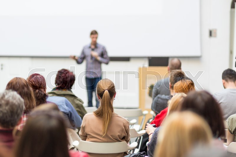 Stock image of 'Male speaker giving presentation in lecture hall at university workshop. Audience in conference hall. Rear view of unrecognized participant in audience. Scientific conference event.'