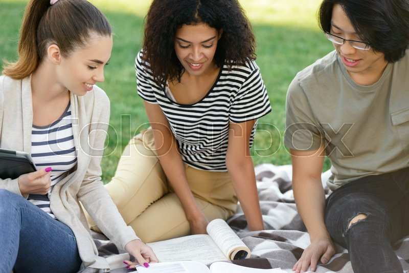 Stock image of 'Photo of multiethnic group of young smiling students studying outdoors. Looking aside.'