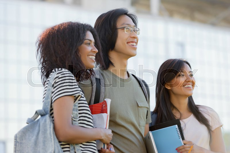 Stock image of 'Image of multiethnic group of young smiling students standing and talking outdoors. Looking aside.'