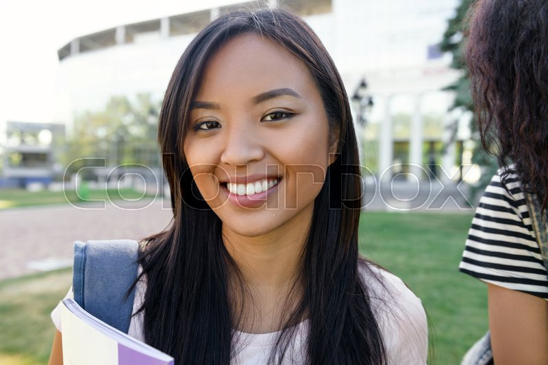 Stock image of 'Picture of young happy student asian woman standing outdoors. Looking camera.'