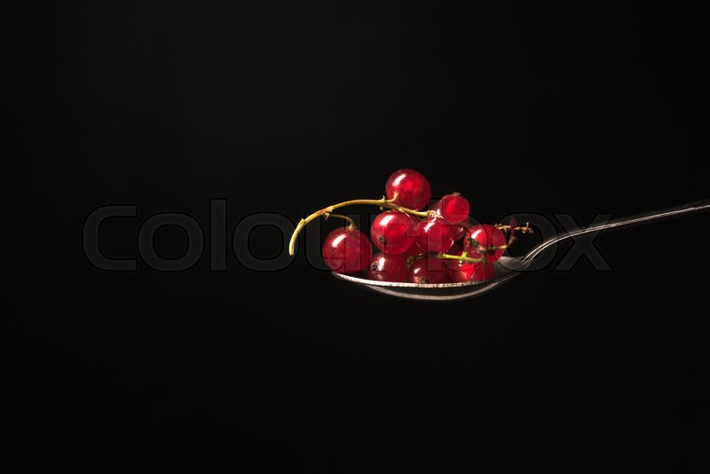 Stock image of 'Spoon with currant isolated over black background.'