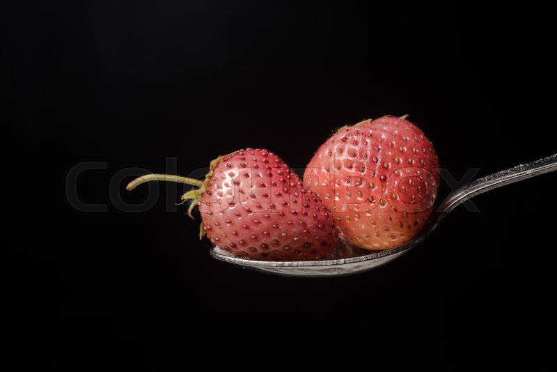 Stock image of 'Spoon with strawberry isolated over black background.'