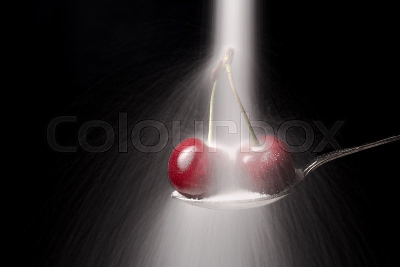 Stock image of 'Sugar pours on the spoon with red cherry isolated over black background.'