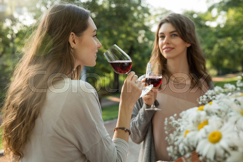 Stock image of 'Picture of pretty young two women sitting outdoors in park drinking wine. Looking aside.'