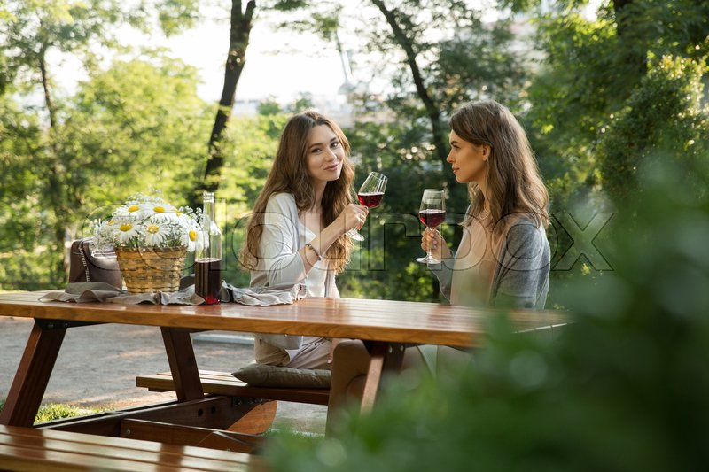 Stock image of 'Picture of pretty young two women sitting outdoors in park drinking wine. Looking camera.'