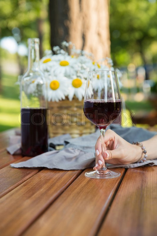Stock image of 'Cropped picture of women sitting outdoors in park drinking wine near flowers.'