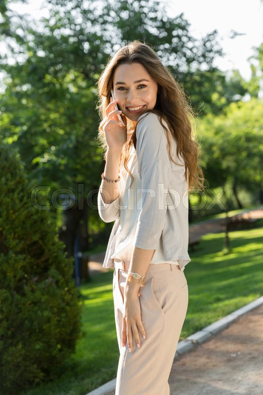 Stock image of 'Picture of cheerful young woman outdoors in park posing. Looking camera talking by phone.'