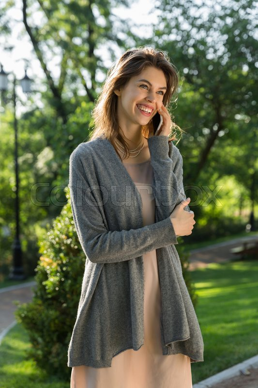 Stock image of 'Image of happy young woman outdoors in park posing. Looking aside talking by phone.'
