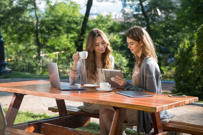 Stock image of 'Photo of smiling young two women sitting outdoors in park drinking coffee using laptop computer. Looking aside.'