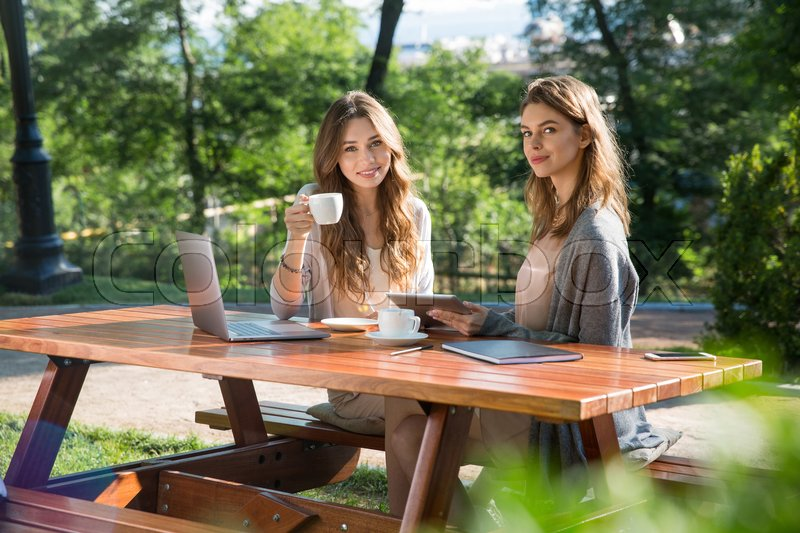 Stock image of 'Picture of pretty young two women sitting outdoors in park drinking coffee using laptop computer. Looking camera.'