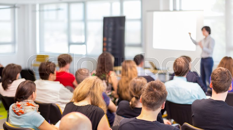 Stock image of 'Business and entrepreneurship symposium. Female speaker giving a talk at business meeting. Audience in conference hall. Rear view of unrecognized participant in audience.'