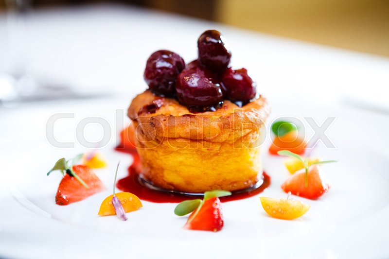 Stock image of 'Sweet cake with cherries on top and fruits served on white plate'