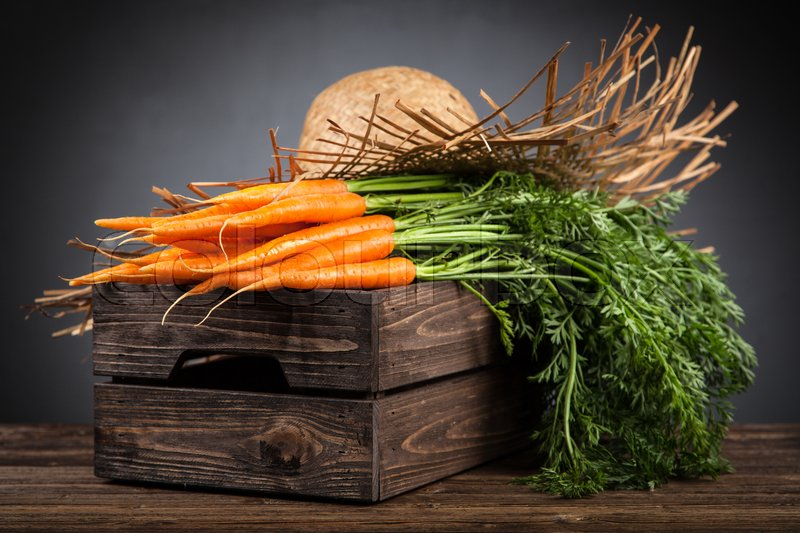 Stock image of 'Fresh organic carrot on wooden table'