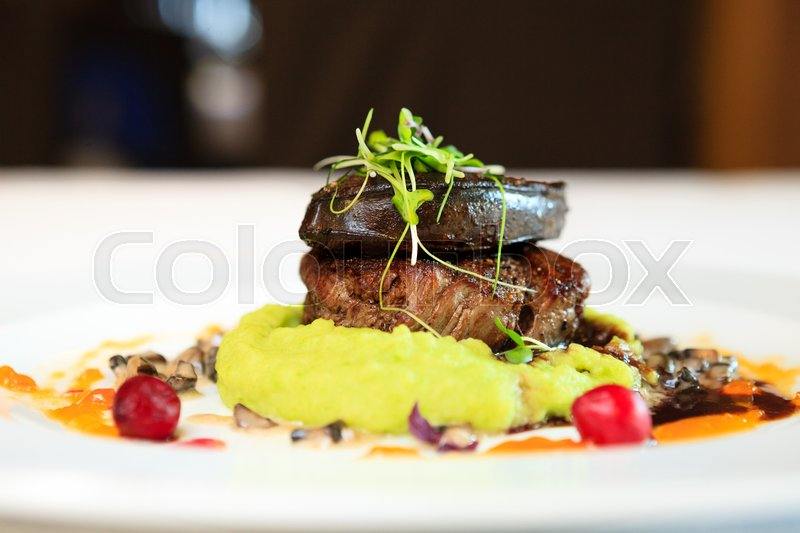 Stock image of 'Fillet of beef with elk liver served with mashed potatoes and peas, creamy mushroom stew and red wine and blueberry sauce'