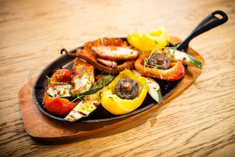 Stock image of 'Pulpo cocido. Boiled octopus, shallots and grilled vegetables'