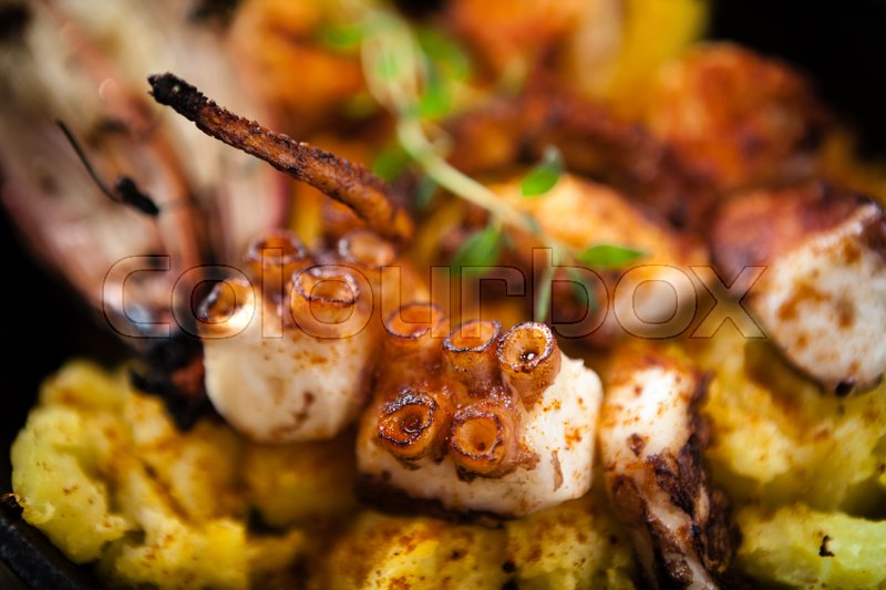 Stock image of 'Pulpo a la gallega. Boiled octopus, baked in a frying pan in a coal stove with potatoes'