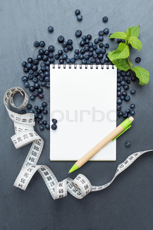 Stock image of 'Blueberries, mint leaves and notepad for writing notes or resolutions, concept of sport, diet, slimming, detox, healthy lifestyles and nutrition. Mock up, space for text.'