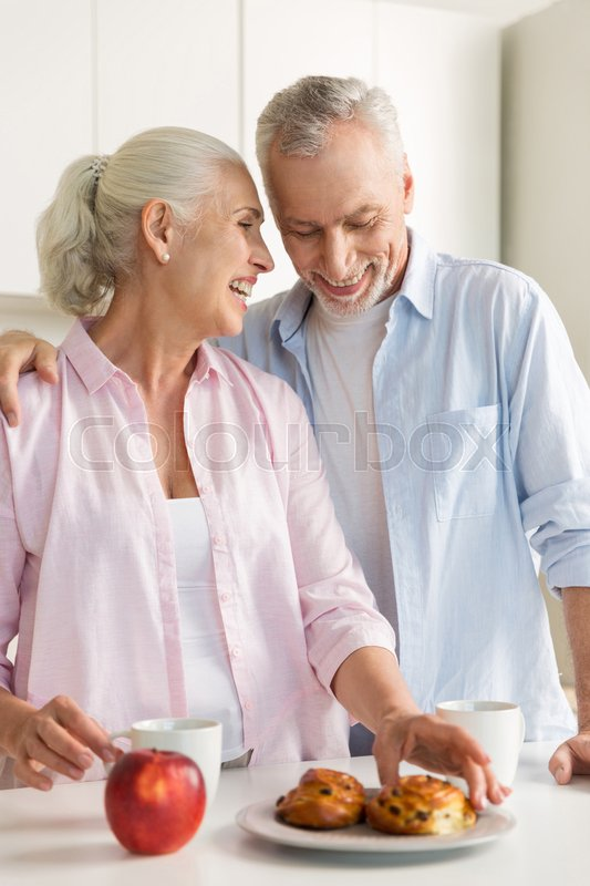 Stock image of 'Photo of smiling mature loving couple family standing at the kitchen near apple and pastries. Looking aside.'
