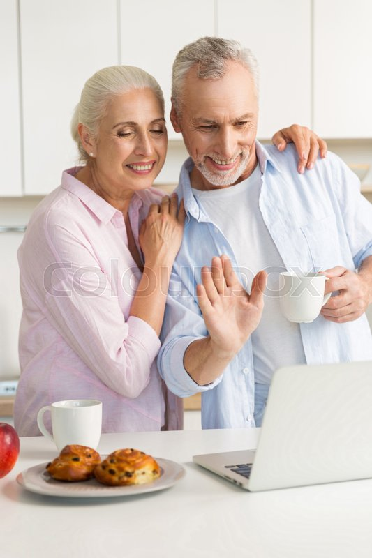 Stock image of 'Photo of cheerful mature loving couple family standing at the kitchen drinking tea eating pastries while using laptop computer. Looking aside.'