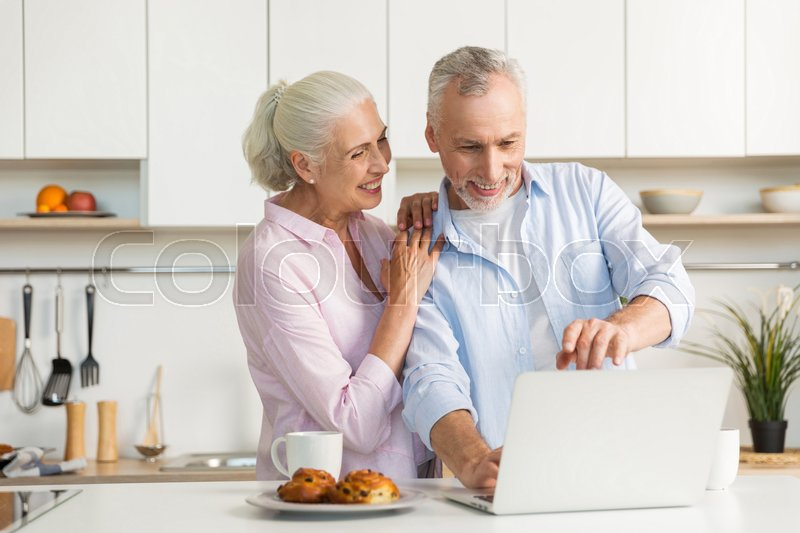 Stock image of 'Image of smiling mature loving couple family standing at the kitchen near tea and pastries while using laptop computer. Looking aside.'