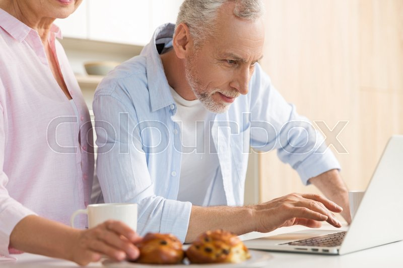 Stock image of 'Photo of cheerful mature loving couple family standing at the kitchen using laptop computer. Looking aside.'