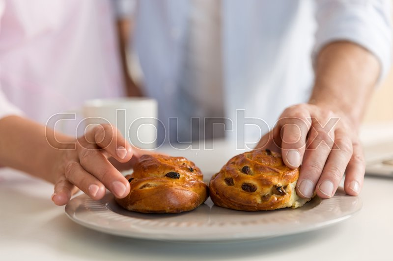 Stock image of 'Cropped photo of mature loving couple family standing at the kitchen near tea eating pastries.'