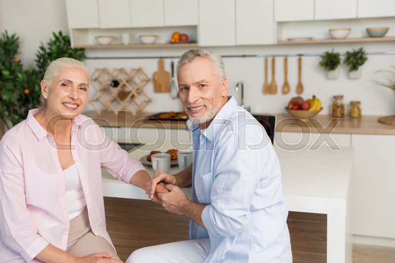Stock image of 'Picture of cheerful mature loving couple family sitting at the kitchen. Looking at camera.'