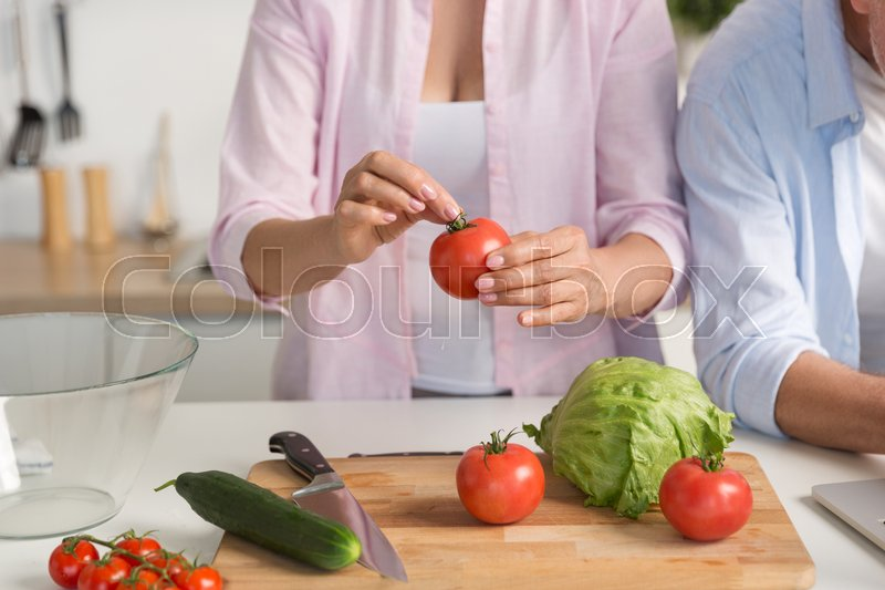 Stock image of 'Cropped picture of mature loving couple family standing at the kitchen cooking.'