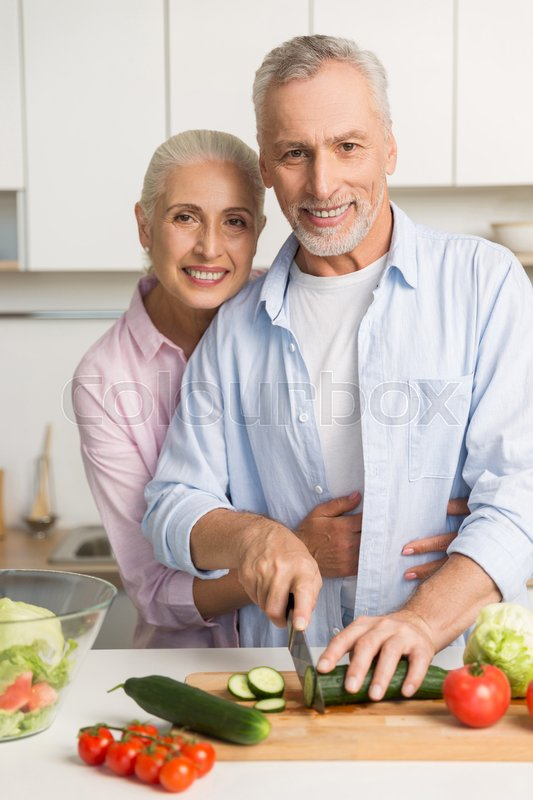 Stock image of 'Image of happy mature loving couple family standing at the kitchen using laptop computer and cooking salad. Looking at camera.'