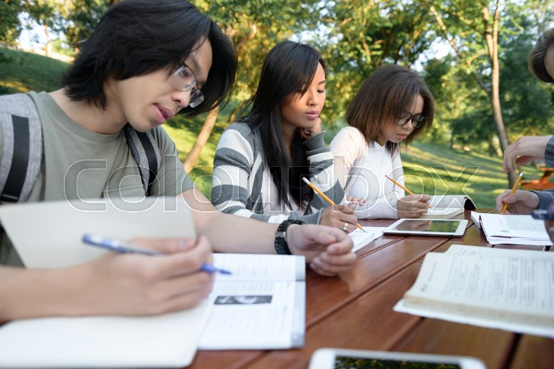 Stock image of 'Multiethnic group of concentrated young people sitting and studying outdoors. Looking aside.'