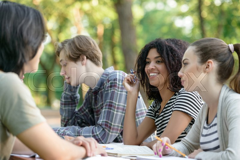 Stock image of 'Image of multiethnic group of happy young students sitting and studying outdoors while talking. Looking aside.'