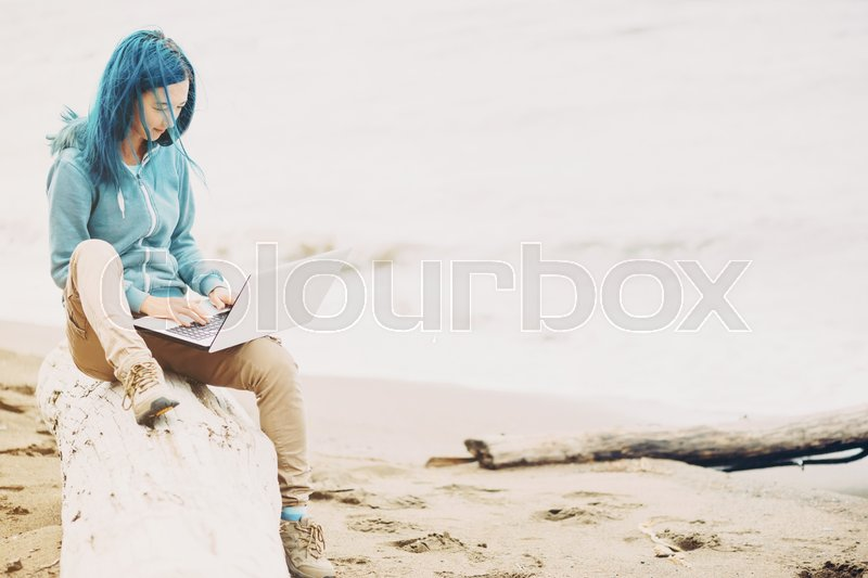 Stock image of 'Freelancer girl sitting on beach and working on laptop near the sea. Freelance concept.'