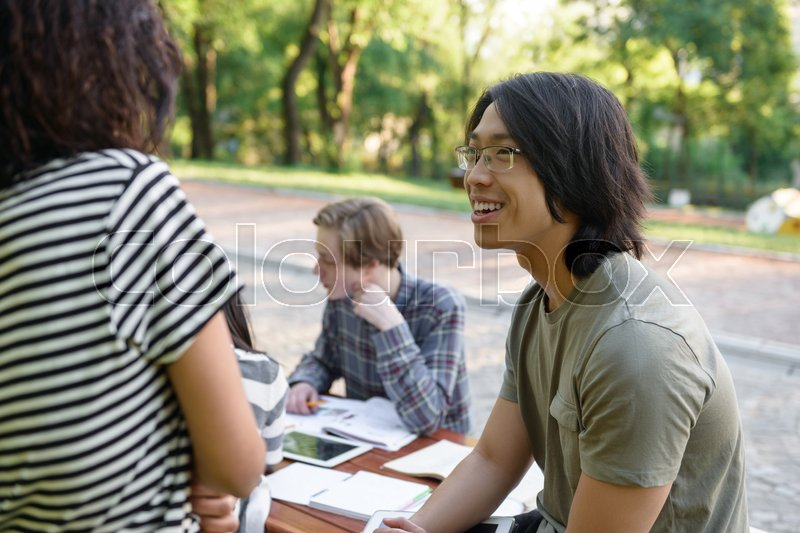 Stock image of 'Photo of multiethnic smiling group of young students sitting and studying outdoors while talking. Looking aside.'