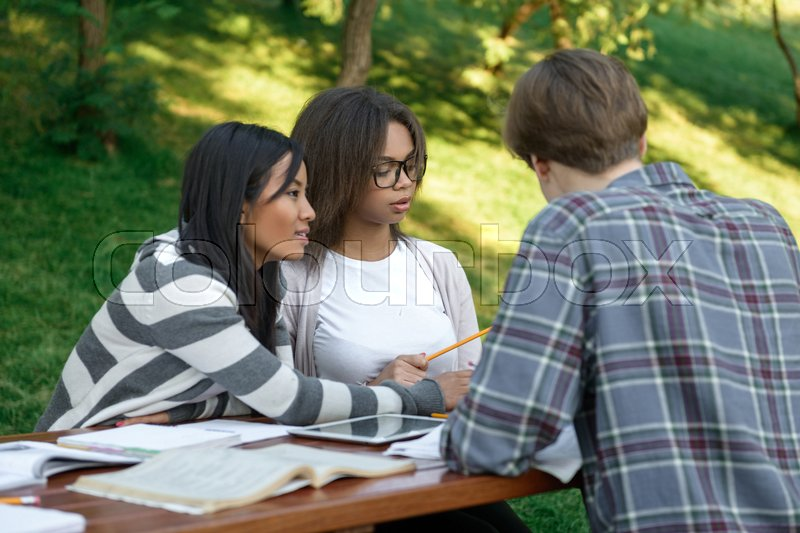 Stock image of 'Image of multiethnic cheerful group of young students sitting and studying outdoors while using laptop. Looking aside.'