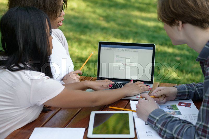 Stock image of 'Image of multiethnic concentrated group of young students sitting and studying outdoors while using laptop. Looking aside.'
